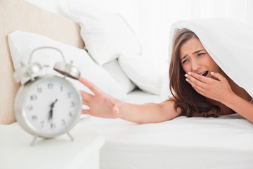 The woman yawns while trying to silence her alarm clock