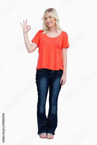Smiling teenager looking at the camera while showing the OK sign