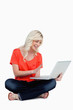 Fair-haired woman waving her right hand in front of her laptop s
