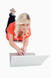 Attractive blonde woman using the touchpad of her laptop while l