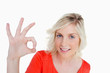 Smiling woman showing the OK sign while looking straight at the