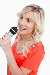 Smiling woman singing with a microphone