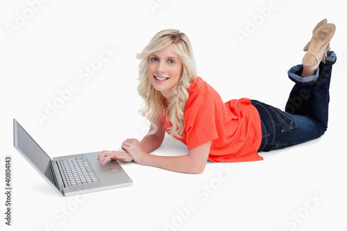 Smiling blonde woman crossing her legs in front of her laptop