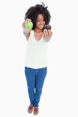 Smiling young woman holding an apple in one hand and a muffin in