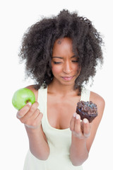 Young woman hesitating between a chocolate muffin and a green ap