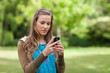Serious teenage girl sending a text while standing in a park
