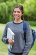 Smiling teenage girl holding a notebook while standing in a park