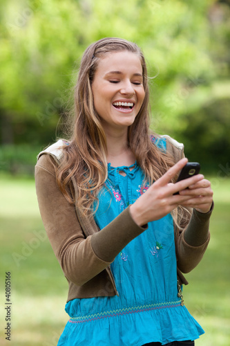 Teenage girl laughing while receiving a text on her cellphone