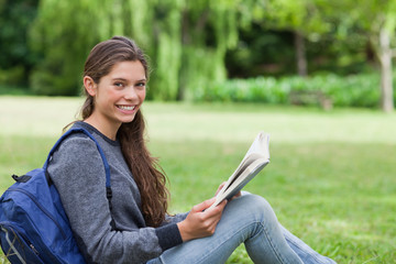 Young smiling girl reading a book while sitting on the grass