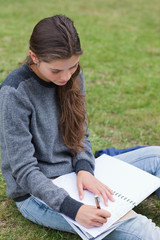 Young serious girl doing her homework while sitting on the grass