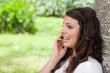 Young woman talking on the phone while leaning against a tree