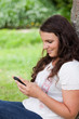 Young relaxed woman sending a text while sitting against a tree
