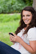 Young smiling woman sitting against a tree while sending a text