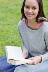 Young smiling woman reading a book in a park while looking at th