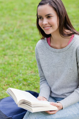 Smiling young woman looking away while holding a book