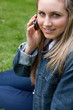 Young smiling girl talking on the phone while sitting down in a