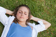 Young relaxed girl napping on the grass while placing her hands
