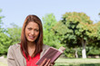 Woman smiling while looking straight ahead with a book in her ha