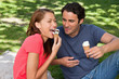 Woman eating ice cream while sitting with her friend