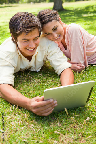 Woman leans against her friend as they use a tablet together