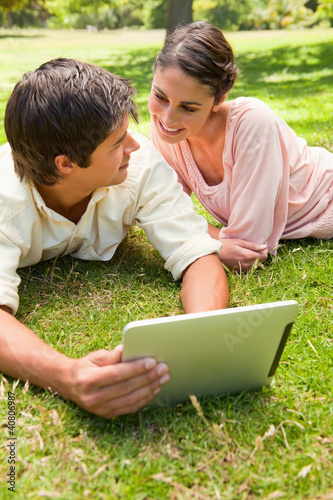 Two friends looking at each other while using a tablet together