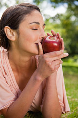 Woman smells an apple while lying in grass