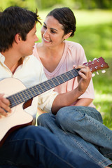 Man playing a guitar while looking at his friend