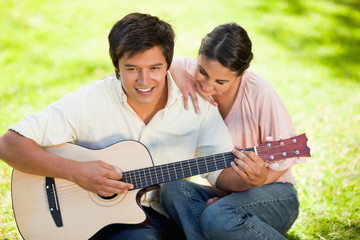 Woman leaning while leaning on her friends shoulder as he plays