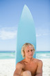 Serious blonde man sitting down in front of his surfboard