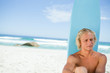 Blonde man sitting in front of his surfboard while looking towar