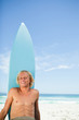 Smiling blonde man sunbathing on the beach with his surfboard ne