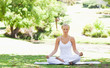 Woman sitting in a yoga position in the park
