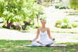Woman sitting in a yoga position on the lawn