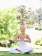 Smiling woman sitting in the park in a yoga position