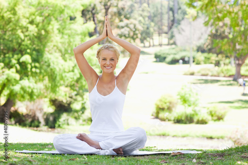 Smiling woman sitting in a yoga position outdoors