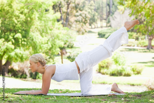 Side view of a woman doing gymnastic exercises on the lawn
