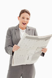 Surprised businesswoman standing reading the newspaper