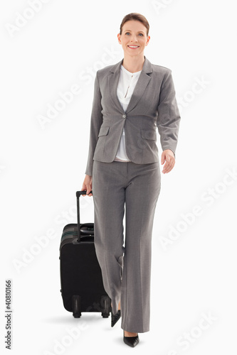 Businesswoman walking forward with a suitcase