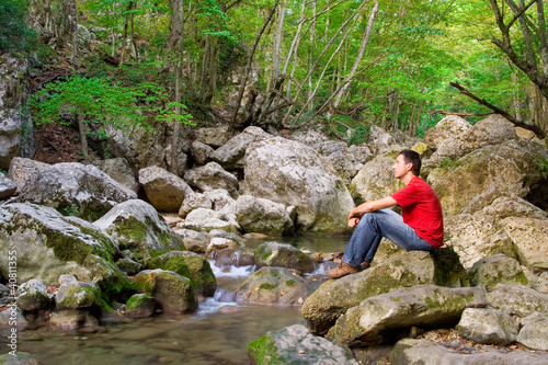 The young man sits at the mountain river