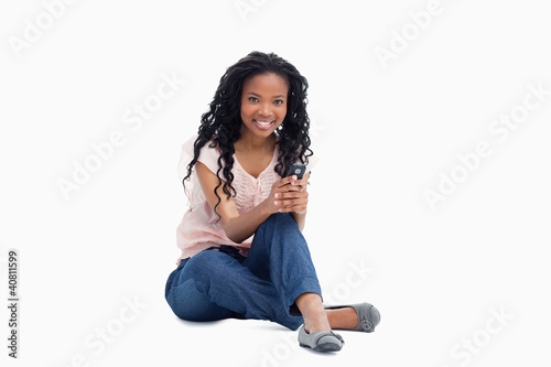 A smiling woman sitting on the floor is holding a mobile phone