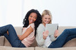 Two women sitting back to back on a couch looking at a tablet co