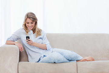 A woman sitting on a couch is holding a mobile phone