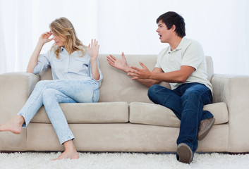 A man is having an argument with his girlfriend while sitting on