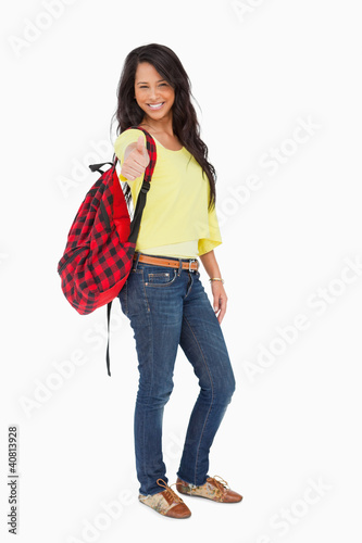 Smiling Latin student thumb-up with a backpack