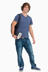 Portrait of a male student with a backpack holding books