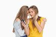Upset young woman looking her cellphone consolded by her friend