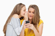 Student whispering to her friend who's texting on her phone