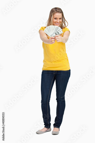Blonde woman smiling while showing a lot of dollars