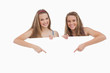 Portrait of young women holding and pointing a blank sign
