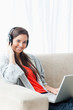 A smiling young woman using a laptop and headphones while lookin